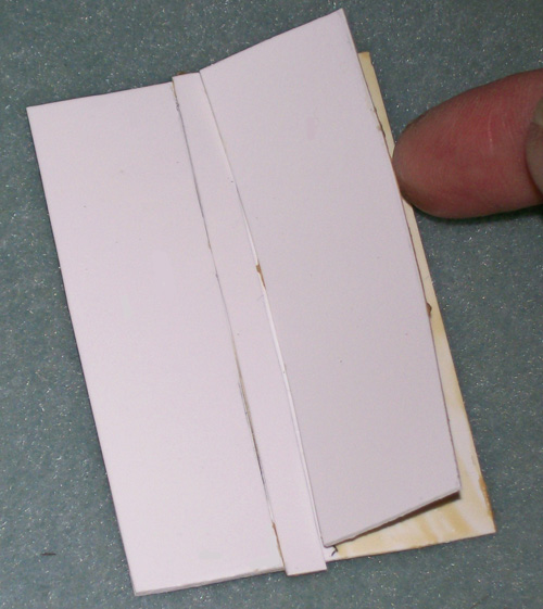 showing the second rectangle applied to the right side of the card, making certain that, as being applied, the edge of the rectangle is being tightly hugged against the temporary 1/4th inch strip.