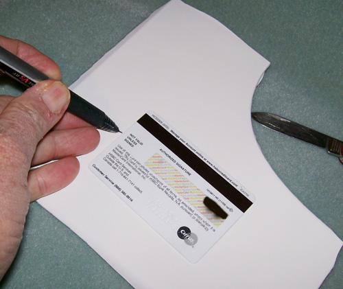 photo of a credit card being used as a guide to mark the boundary area of the plastic to be cut.