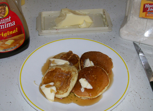 Photo of apple pancakes with butter and maple syrup.