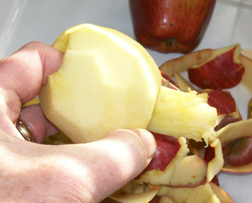 Photo of a peeled apple with the core being pushed out.