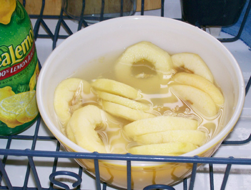 Photo of a sliced apples soaking in ReaLemon water.