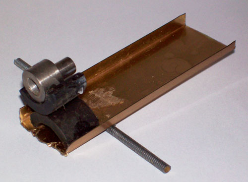Rear view photo showing a home made, teeter-totter style balance scale for penny sorting.